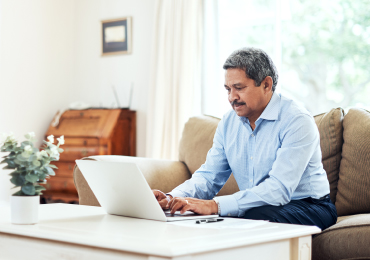 Man using laptop in home living room
