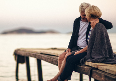 Mature couple sitting on lake dock