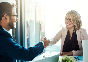 man and woman shaking hands in office setting